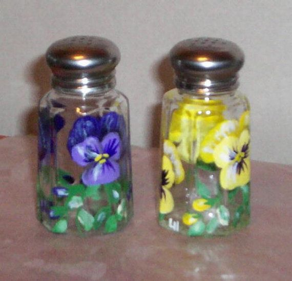These medium size 1-1/4 ounce clear glass Salt & Pepper Shakers feature Purple & Yellow Pansies on both shakers; individually hand-painted by