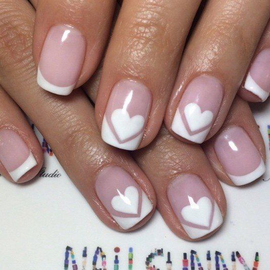 White french manicure with white hearts on the middle and index finger nails