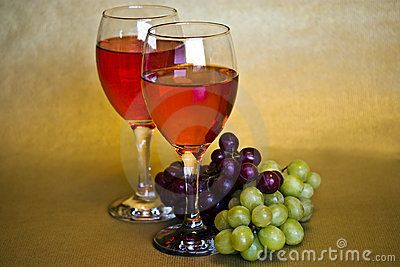 a still life of two glasses of red  wine and two bunches of grapes