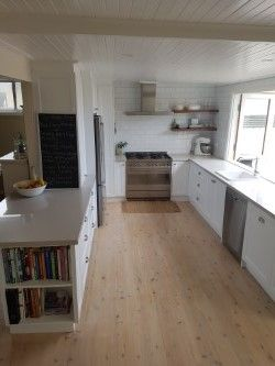 Classic White Kitchen. Shaker style doors. White Subway tile with grey grout. Wooden floating shelves. Grey iron bark shelves. Nordic Loft Caeserstone. Lime washed timber floors. V-joint ceiling. Bi-fold windows.Kitchen Blackboard. Cookbook nook. 90cm Smeg Oven. IKEA sink and tapware.