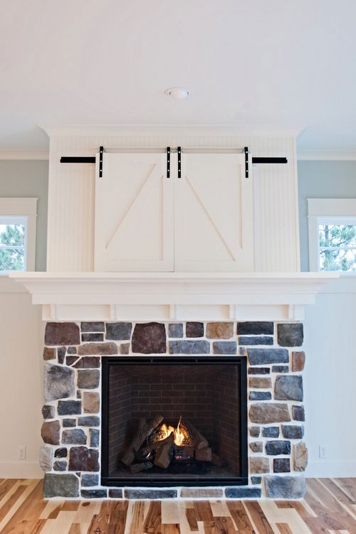 Custom barn doors hide tv above fireplace by gowler homes Hide fireplace ideas