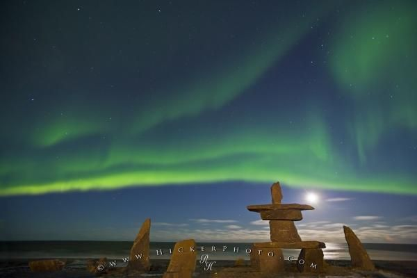 Photo of Northern Lights, Aurora borealis, above an inukshuk in the town of Churchill with a moon above Hudson Bay, Manitoba.