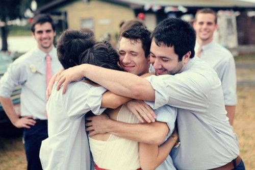 Groomsmen hugging the bride. Love this!