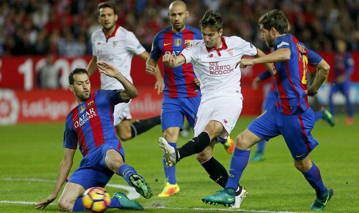 El delantero argentino del Sevilla, Luciano Vietto (2d), golpea el balón ante los jugadores del F. C. Barcelona, el centrocampista Sergio Busquets (i) y el defensa Sergi Roberto (d), durante el encuentro
