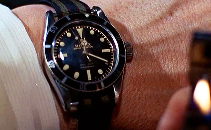 This screen shot shows Sean Connery's Big Crown Rolex Submariner (Ref. 6538, 38mm case) on a (navy blue, olive and burgundy) regimental nylon strap. Note loose fitting 16mm nylon strap ('not' a NATO) on 20 mm lug width. (Click on photo for high-res. image.) Photo found here: http://rolexblog.blogspot.com/2010/03/rolex-introduces-all-new-supercase.html  More info. on the 'Bond Strap' can be found here: http://rolexblog.blogspot.com/2009/07/real-james-bond-watchstrap-comes-to.html: Rolex Watches, Bond Watches, Style, James Bond, James D'Arcy, Rolex Submariner, Sean Connery, Bond S Rolex
