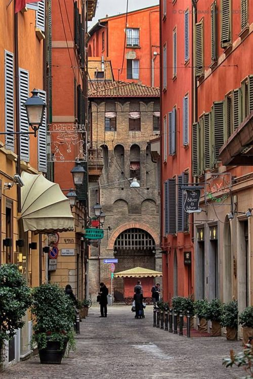 Bologna, Italy. Love the pallets of oranges!! Lovely street@