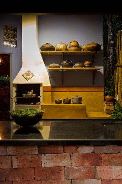 O espaço gourmet criado pelo escritório Mmmundim foi inspirado nas residências do interior de Minas Gerais. Valorizando o gosto da moradora, que é chef de cozinha, o ambiente conta com churrasqueira, fogão a lenha e bancada de tijolo de adobe.