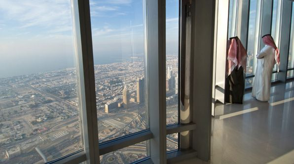 Two men view Dubai's business district from the Burj Khalifa, an enormous structure that cost $1.5 billion to build.