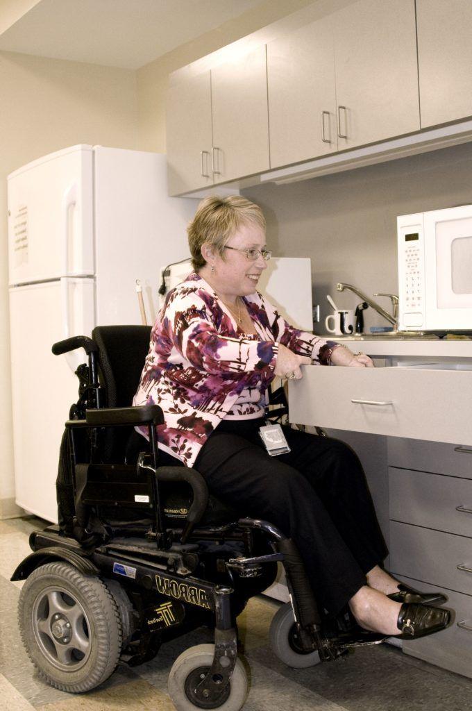 Femme en fauteuil roulant dans une cuisine adaptée.