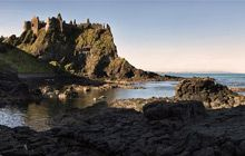Dunluce Castle is located dramatically close to a headland that plunges straight into the sea, along the North Antrim coast in Northern Ireland.