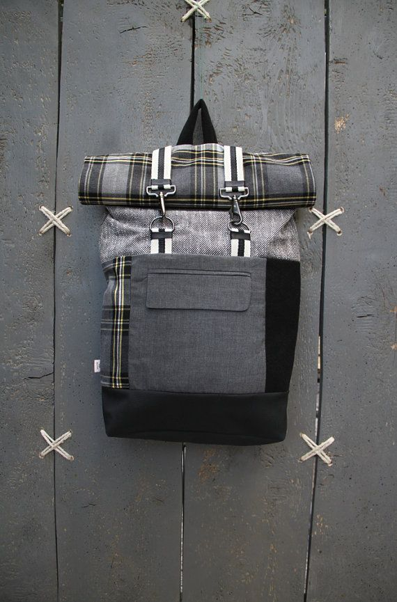 Black and grey roll top rucksack with a pocket from men's suit jacket in the…