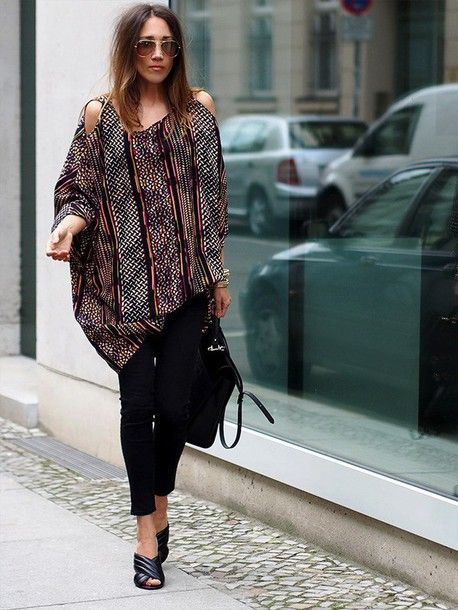 An oversized cut out shoulder printed blouse in combination with a pair of black skinny jeans, mules and large handbag. For a casual, off-duty vibe.