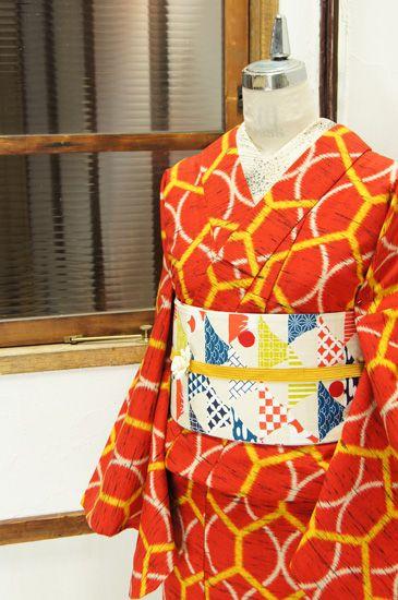 ポピーレッドに白の網目模様と黄色い亀甲繋ぎが重ねられたウールの単着物です。