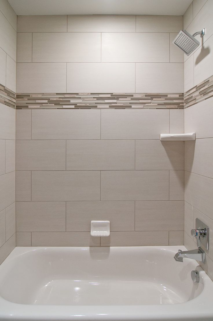 We love oversized subway tiles in this bathroom! The addition of glass  accent tiles gives the space a custom