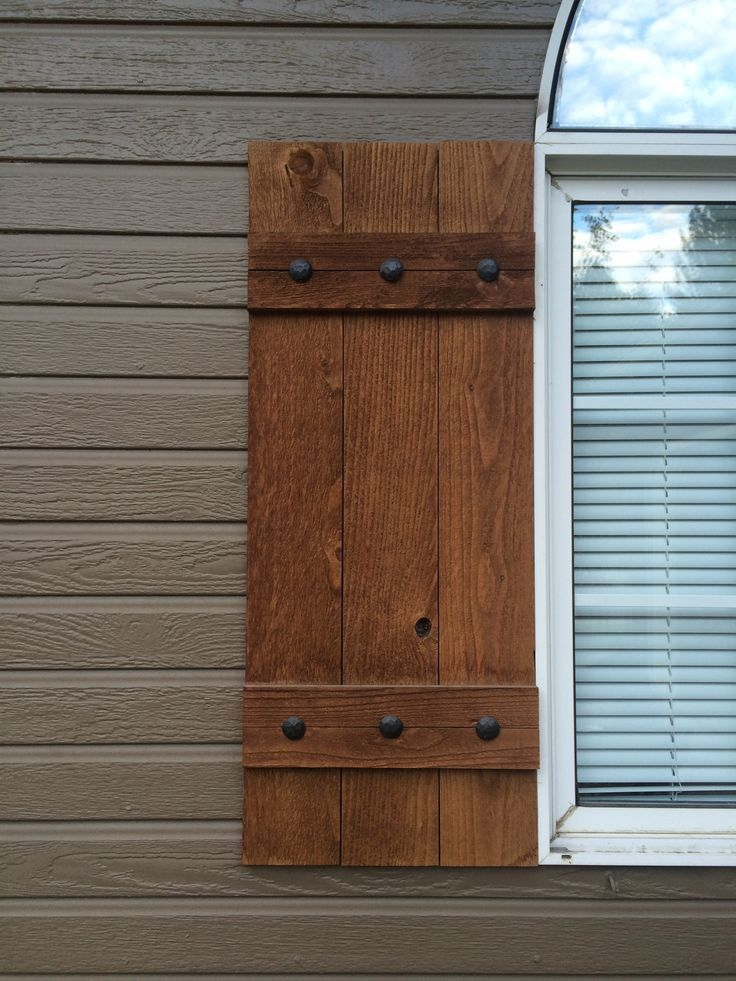 Homemade shutters.  Stained wood. Decorative nails from ebay.