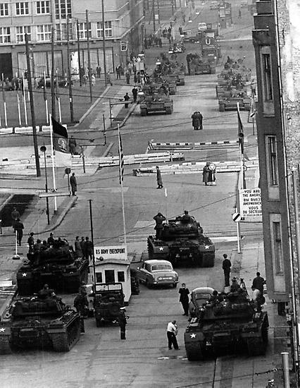"""Die Welt hält den Atem an, als sich im Oktober 1961 für kurze Zeit sowjetische und US-amerikanische Panzer am """"Checkpoint Charlie"""" gegenüberstehen. Auslöser war der Versuch der SED-Führung, alliiertes Recht der Westmächte in Berlin einzuschränken."""