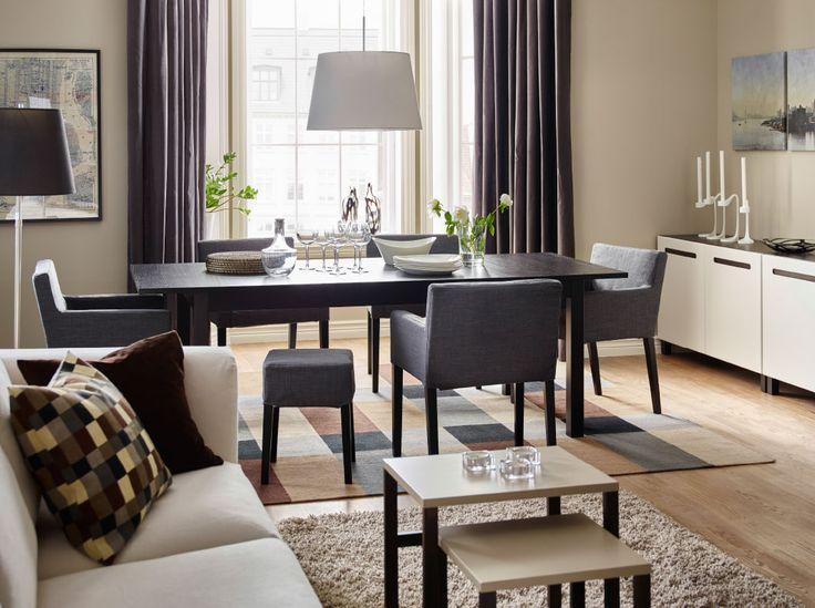 Zona pranzo con tavolo marrone-nero abbinato a sedie con braccioli e poggiapiedi grigio scuro.