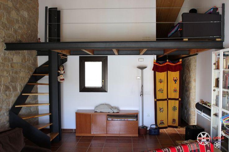 Escala de caragol amb esglaons de fusta i altell de disseny amb acer pintat de forja i barana de sirga horitzontal