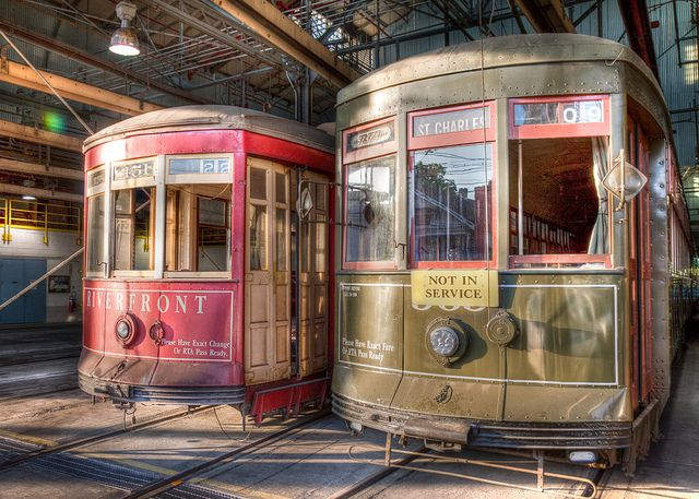 new orleans streetcars . the red cars are new . the green cars are historic . don't mistake it!