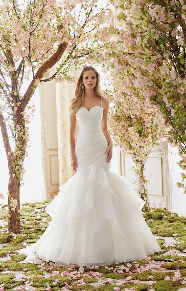 Asymetrycznie drapowany gorset i falbany sukni Mori Lee typu rybka. Romantyczna suknia ślubna,zaznaczająca talię i ujmująca centymetry, dzięki licznym drapowaniom. …