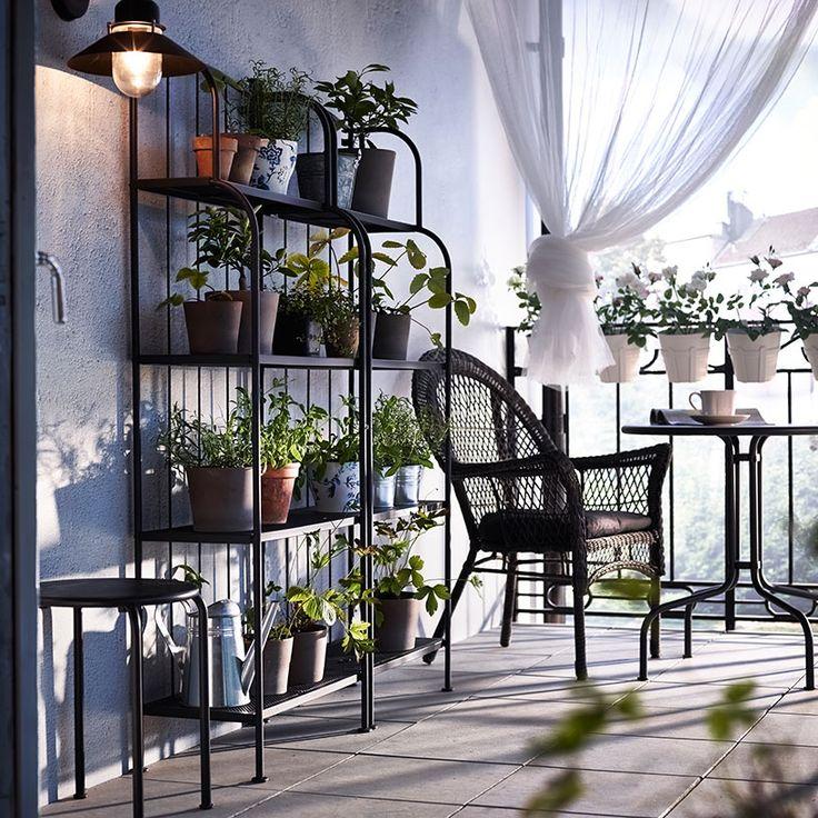 Ein kleiner Balkon mit LÄCKÖ Regalen, LÄCKÖ Sessel mit Kissen und Tisch in Grau, in den Regalen viele Pflanzen in MANDEL Übertöpfen in Graubraun