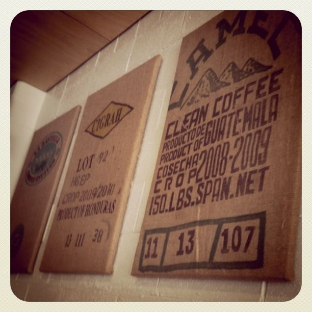 stretched coffee bags... good idea *Very cheap wall solution, although I think they would have looked better framed.