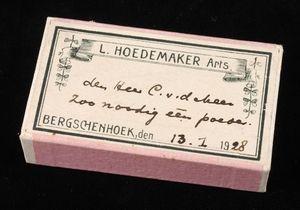 """Rechthoekig kartonnen pillendoosje """"L. Hoedemaker Arts., Bergschenhoek"""" met handgeschreven tekst en roze zijkant."""