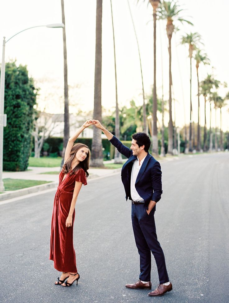 Red velvet dress by Reformation || What to wear for your engagement photos || Beverly Hills engagement session || Blue skinny suit || Cute engagement photo ideas || Rodeo Drive || Dancing in the streets || engagement photography