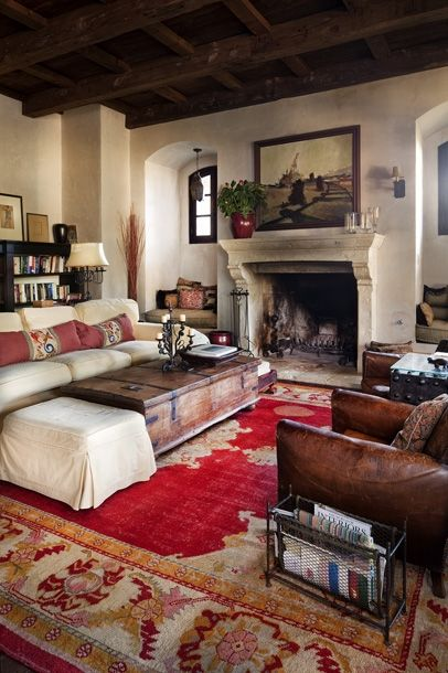 Neutral Mediterranean / Spanish vibe living room with white sofa, leather chair, stone fireplace mantle, traditional oriental red rug