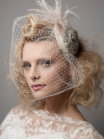 Diamond Dove with feathers & birdcage veil - The eye-catching silver crystal embellishment adorns a circular base of ivory lace. This Twenties inspired piece is finished with a trim of  blush ostrich feathers.