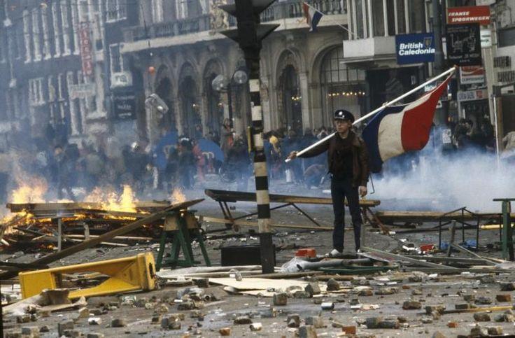 30 april 1980 | Een kraker staat met een vlag temidden van een enorme ravage het Rokin tijdens de rellen bij de inhuldiging van koningin Beatrix. De kraakbeweging greep de kroning aan om te protesteren tegen het woningbeleid van de gemeente Amsterdam, onder het motto 'Geen woning geen kroning'.