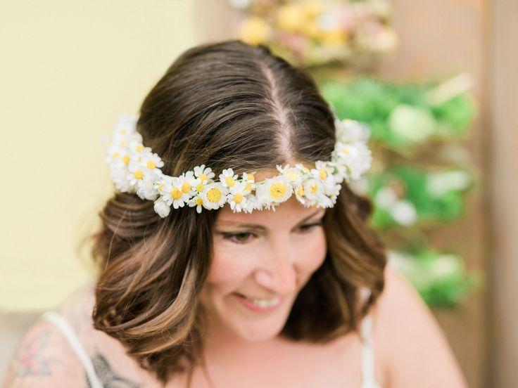 I håret har bruden en bohemisk blomsterkrans bunden med söta matricaria. Till en enkel brudklänning blir blommor i utsläppt och lockigt hår en fin detalj.