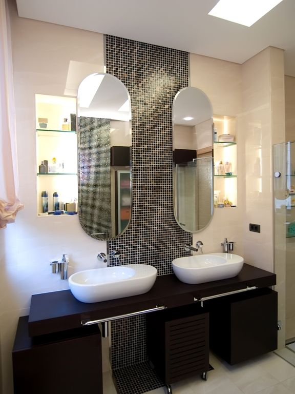 Black mosaic used as feature between his and hers mirrors in the bathroom.