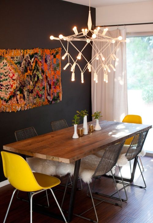 reclaimed wood table on metal legs, yellow Eames chairs from eBay, metal wire chairs from CB2. Patrick Townsend chandelier, boucherouite rug turned wall hanging. Paint: Rust-Oleum Latex Chalkboard Paint