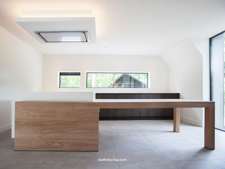 Creating a balanced kitchen area by combining contrasting materials. Heavy textured oak veneer matched with matte white HI-MACS (solid surface). A royal 5.40 meter bespoke wall-to-wall countertop, seamlessly joined together at just 12 milimeters thick. Curious about our made to measure kitchen solutions? Contact us at sales@bathsbyclay.com #bathsbyclay #madetomeasure #HIMACS #kitchendesign #designwithoutcompromise