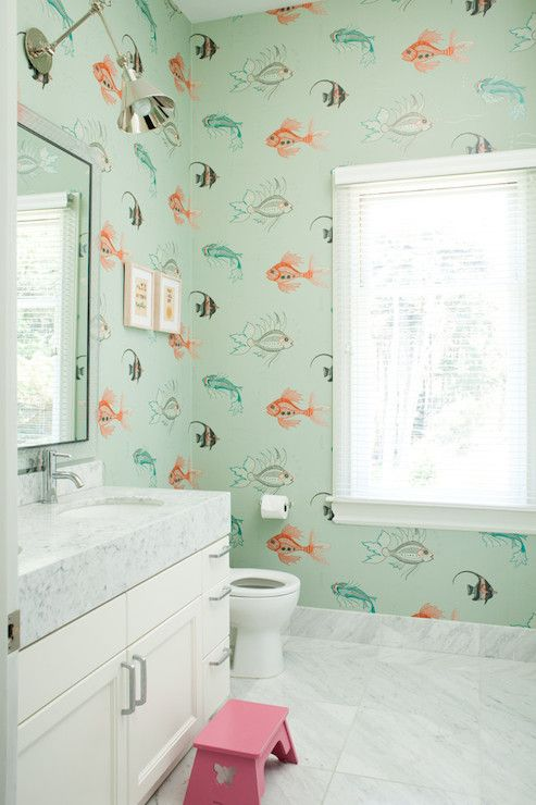 Kids' bathroom features fish wallpaper, Nina Campbell Aquarium Wallpaper, framing polished nickel swing-arm sconce over framed mirror over ivory washstand with thick marble countertops and oval sink accented with modern faucet paired with pink step stool over marble tiled floor.