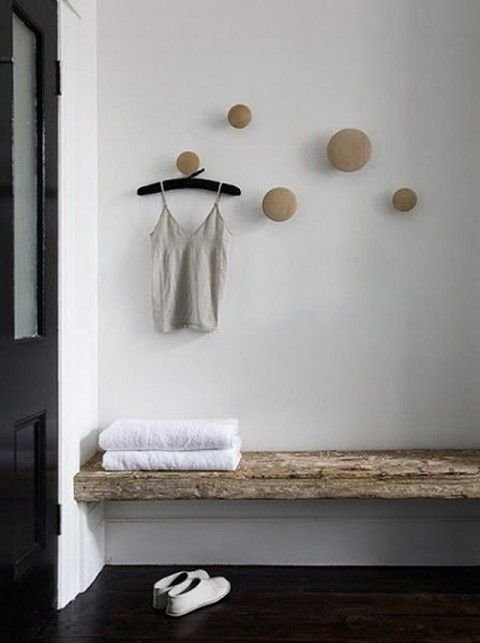Varied sizes of wooden knobs used as hooks.  Such a great idea for a bathroom or even entrance area.