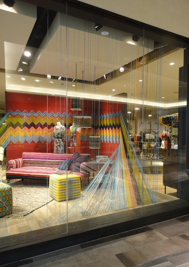 i heart interiors: Anthropologie Window Display - The Neverending Afghan; Maybe not this long, but v. cool idea to use afghan as wall border/decor.