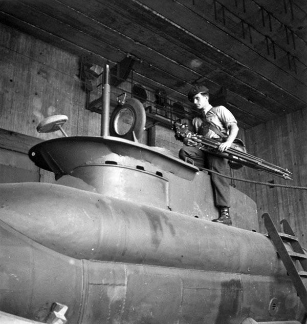 Sergeant A.H. Calder of the Canadian Army Film and Photo Unit, who carries a camera and tripod, examining one of the German miniature two-man submarines discovered in a shipyard at Kiel, Germany, 18 May 1945. LAC.