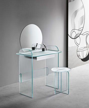 Toeletta composta da specchio, piano d'appoggio e cassetto, disponibile in vetro opalina verde, satinato o fumè. Possibilità di personalizzare il cassetto con rivestimento in pelle.
