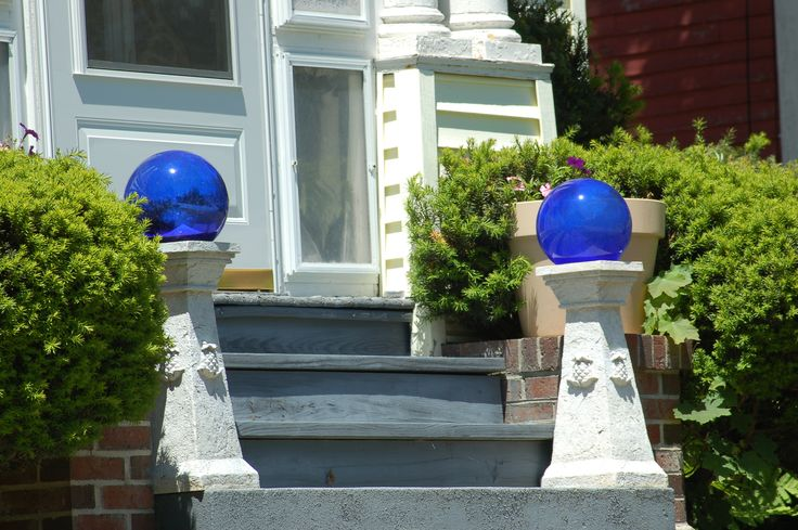 Blue gazing balls on classy pedestals grace this front entry. As is often the case with front entrance decorations, symmetry is employed. See more ideas for landscaping around front-door entries at http://landscaping.about.com/od/galleryoflandscapephotos/ig/front_door_entrances/