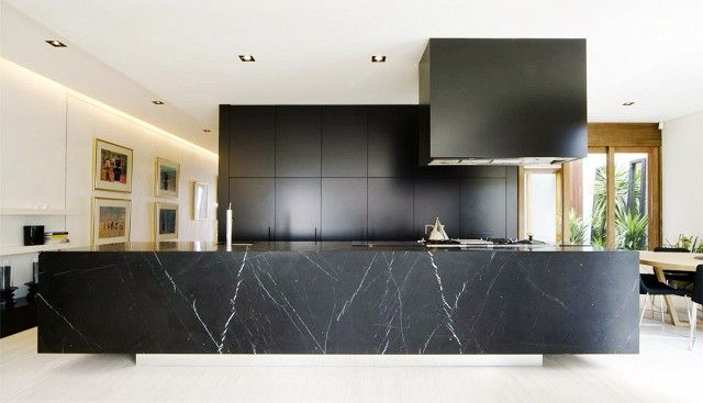 An impressively oversized counter in hypnotic black marble has a gallery-like sculptural effect in this kitchen.