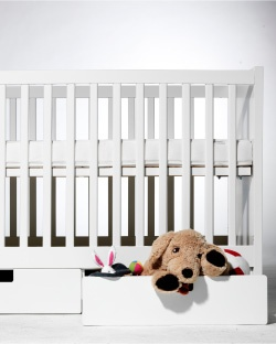 A white STUVA crib with built-in drawers for extra storage