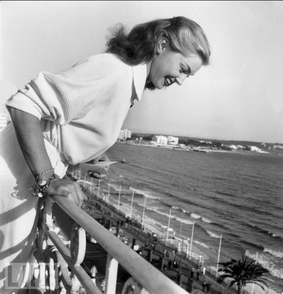 Esther Williams, famous for her swimming movies, throws autographs off a balcony to her fans during the Cannes Film Festival on April 27, 1955.