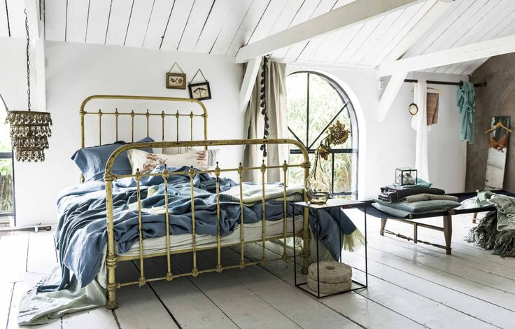 Vintage attic bedroom with white wooden beams and floor