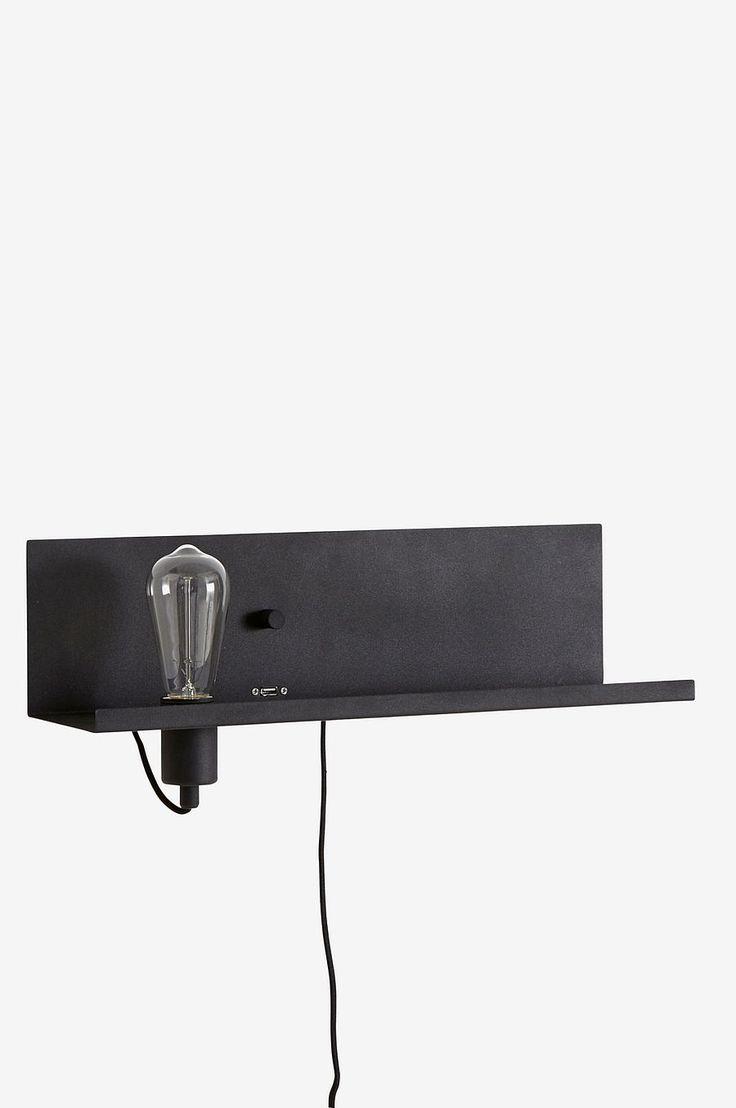 Vägglampa med ett litet hyllplan. Av matt svartmålad metall med inbyggd dimmer /strömbrytare och USB-uttag för laddning av smartphone eller surfplatta. Höjd 13,5 cm, bredd 50 cm, djup 17,5 cm. Sladd med strömbrytare och väggkontakt, sladdlängd 2 m. Stor sockel E27. Max 60 W eller motsvarande styrka i halogen, lågenergi eller LED. Ljuskälla ingår ej. Olika typer av ljuskällor kan ha stor påverkan på stil och utseende hos lampan. Prova dig fram till ditt eget uttryck!