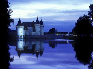 Castillo reflejado en el agua al anochecer
