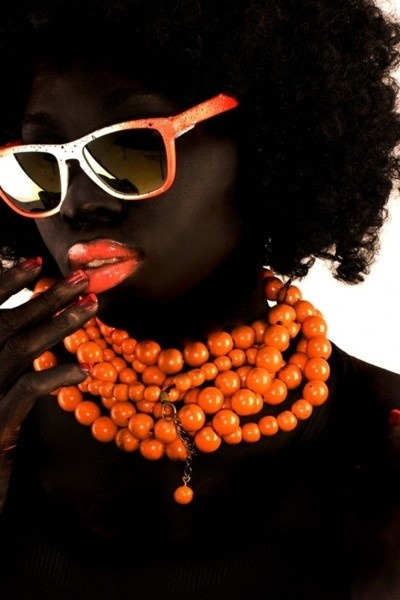 Brown beauty - dark brown-skinned girl, with afro-curly hair, bright chunky mandarin colour necklace, orange lips and sunglasses.