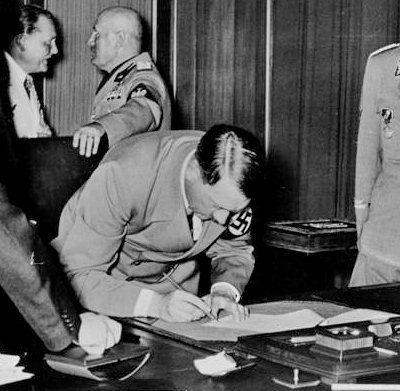 Hitler signs the Munich Agreement on September 30th. Behind him Mussolini is seen chatting with Hermann Göring.