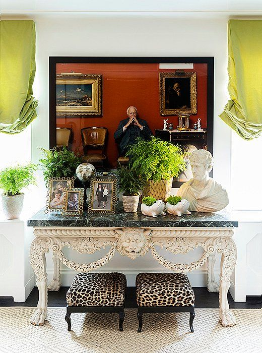"Bridging the gap between the contemporary and the traditional, a pair of leopard-print ottomans rest beneath a George II marble topped console and a Tina Barney photograph. ""Sometimes people think he's part of the family,"" Kate says with a laugh of the pensive character framed in black, ""and we're okay with that."""